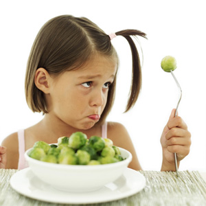 child frowning at brussels sprouts