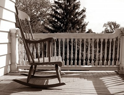 1718009-rocking-chair-on-an-old-house-porch